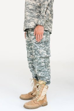 Partial view of male soldier in camouflage clothing and boots on grey background stock vector