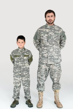 Father and son in military uniforms looking at camera on grey background stock vector