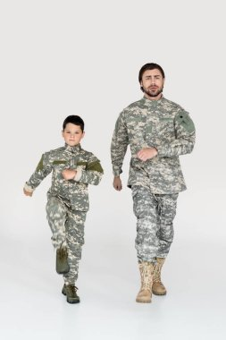 Father and son in military uniforms marching and looking at camera on grey background stock vector