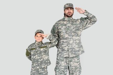 portrait of confident soldier and son in military uniforms saluting isolated on grey