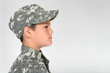 Side view of little kid in military uniform posing on grey background stock vector