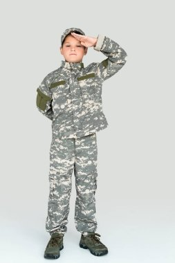little kid in military uniform looking at camera and saluting on grey background