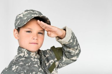 portrait of little kid in military uniform saluting on grey background