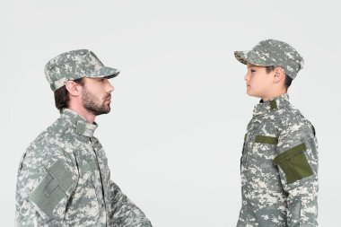 Side view of soldier and son in military uniforms looking at each other isolated on grey stock vector
