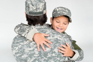 Partial view of father and smiling son in military uniforms hugging each other on grey background stock vector