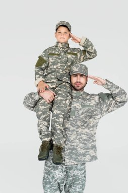 soldier holding son in military uniform on shoulder and saluting isolated on grey