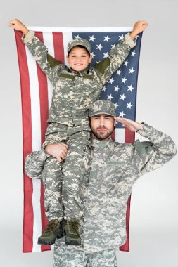 portrait of smiling boy with american flag sitting on fathers shoulder in military uniform on grey background