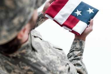 partial view of male soldier in military uniform with american flag in hands