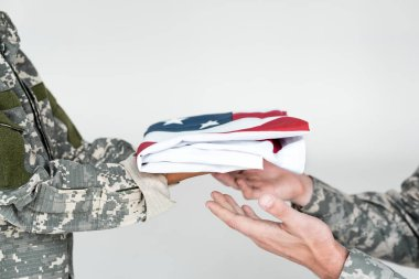 Cropped shot of kid in camouflage clothing giving folded american flag to soldier on grey background stock vector