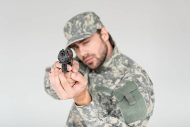 Selective focus of male soldier in military uniform holding gun isolated on grey stock vector