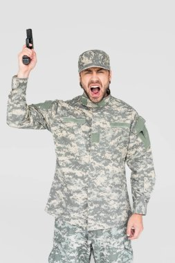 Screaming male soldier in military uniform holding gun isolated on grey stock vector