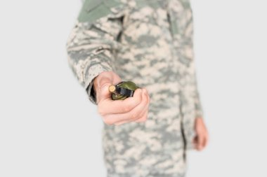 Cropped shot of soldier holding grenade in hand isolated on grey stock vector