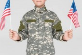 cropped shot of child in military uniform with american flagpoles in hands isolated on grey