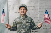 portrait of smiling kid in camouflage clothing holding american flagpoles with grey brick wall on backdrop