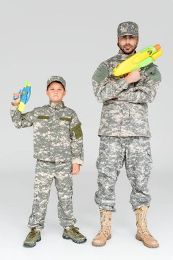 Father and son in military uniforms with toy water guns on grey background stock vector
