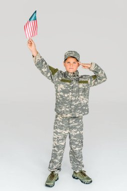 little boy in camouflage clothing saluting while holding american flagpole in hand isolated on grey