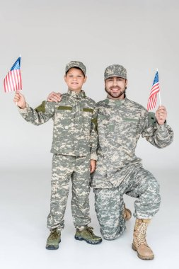 smiling father and son in camouflage clothing with american flagpoles in hands on grey background