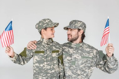 Portrait of smiling father and son in camouflage clothing with american flagpoles in hands isolated on grey stock vector