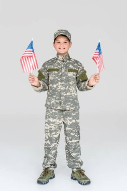 Smiling child in military uniform with american flagpoles in hands looking at camera on grey backdrop stock vector