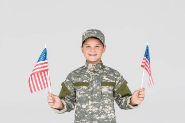 portrait of smiling child in military uniform with american flagpoles in hands isolated on grey