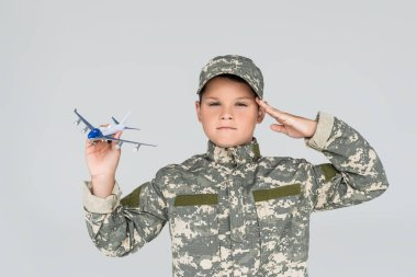 Portrait of little boy in military uniform with toy plane in hand saluting isolated on grey stock vector