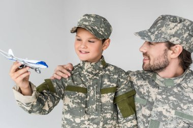 Portrait of father and son in military uniforms with toy plane isolated on grey stock vector