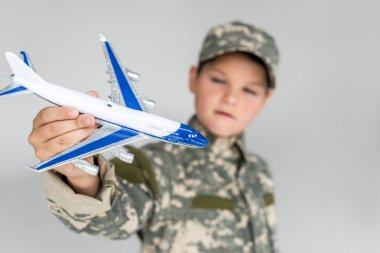 Selective focus of little boy in military uniform with toy plane in hand isolated on grey stock vector