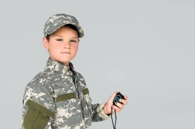 Portrait of kid in military uniform with stop watch in hand looking at camera isolated on grey stock vector