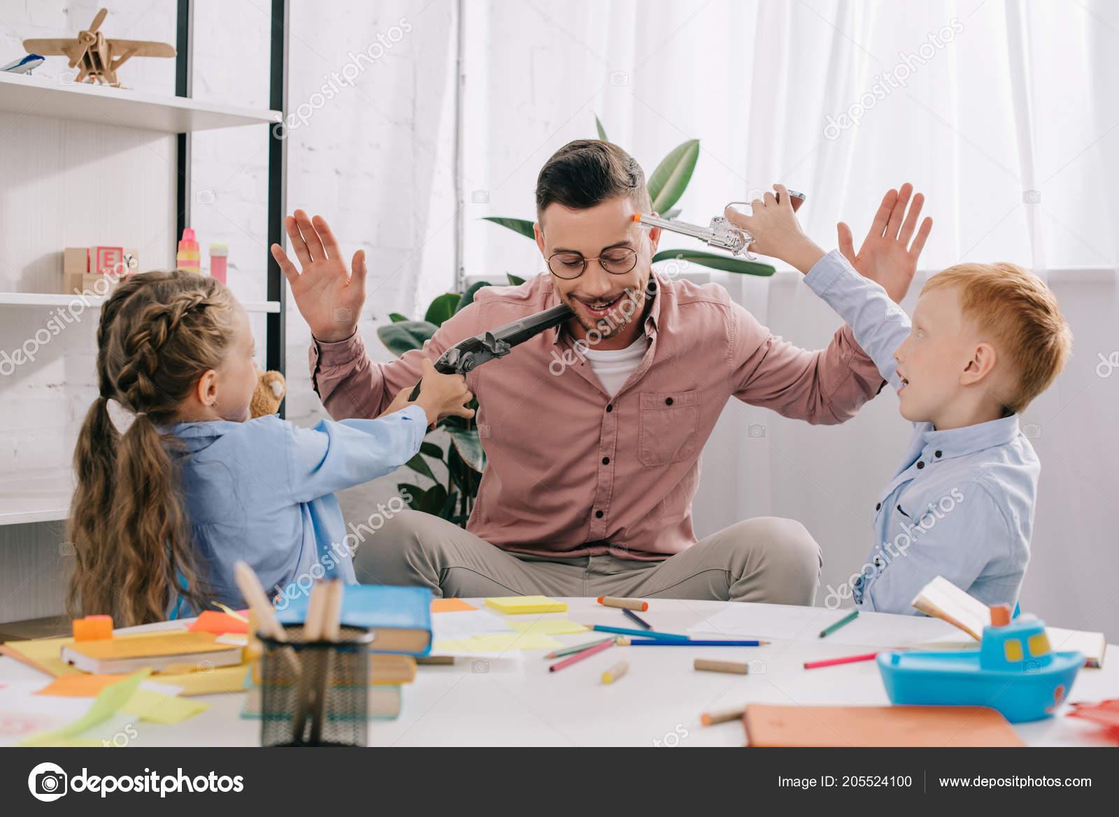 Insegnante occhiali vista con mani ragazzi con pistole giocattolo