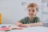 portrét preschooler sedí u stolu s barevné tužky v učebně