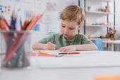 Fotografie portrait of preschooler drawing picture with pencils at table in classroom