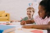 Fotografie Selektivní fokus multikulturní Preschoolers u stolu s papíry a tužky v učebně