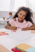 Selektivní fokus úsměvu africké americké dítě u stolu s papíry a pastelky na malování v učebně