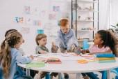 Fotografie Interracial děti sedí u stolu s papíry a barvy pro kreslení v učebně