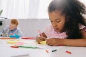 Selektivní fokus multikulturní Preschoolers kreslení obrázků s tužky v učebně