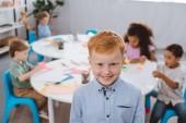 Fotografie Selektivní fokus šťastný zrzavé vlasy chlapce s mnohonárodnostní spolužáky za v učebně při pohledu na fotoaparát