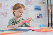Fotografie cute preschooler with pink paper sitting at table in classroom
