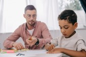 Fotografie caucasian teacher and african american boy drawing picture together in classroom