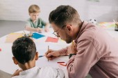 Fotografie selective focus of teacher and multiracial boys drawing pictures with colorful pencils at table in classroom
