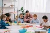 Fotografie učitel a interracial předškoláky u stolu s barvy a papíry v učebně