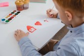 partial view of preschooler red hair boy drawing picture at table in classroom