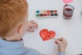 částečný pohled preschooler červené vlasy chlapce kreslení srdce na papír u stolu v učebně