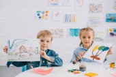 Fotografie portrait of cute kids showing drawings in hands at table in classroom
