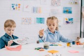 Fotografie focused preschoolers drawing pictures with paints and paint brushes at table in classroom