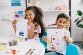 portrét šťastné africké americké děti ukazovat obrázky v učebně u stolu
