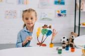 kis gyerek találat színes képet a szobában asztalnál ülve kezébe portréja