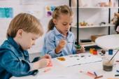 Fotografie cílené předškolní kreslení obrázků s barvami a malířských štětců v učebně u stolu