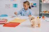 Fotografie Selektivní fokus hračka ovce a kluk kreslení obrázek u stolu v pokoji