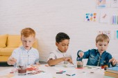 Fotografie portrait of multiethnic kids with paint brushes drawing pictures in classroom