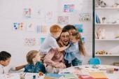 Fotografie Interracial děti objímání šťastný učitel u stolu v učebně